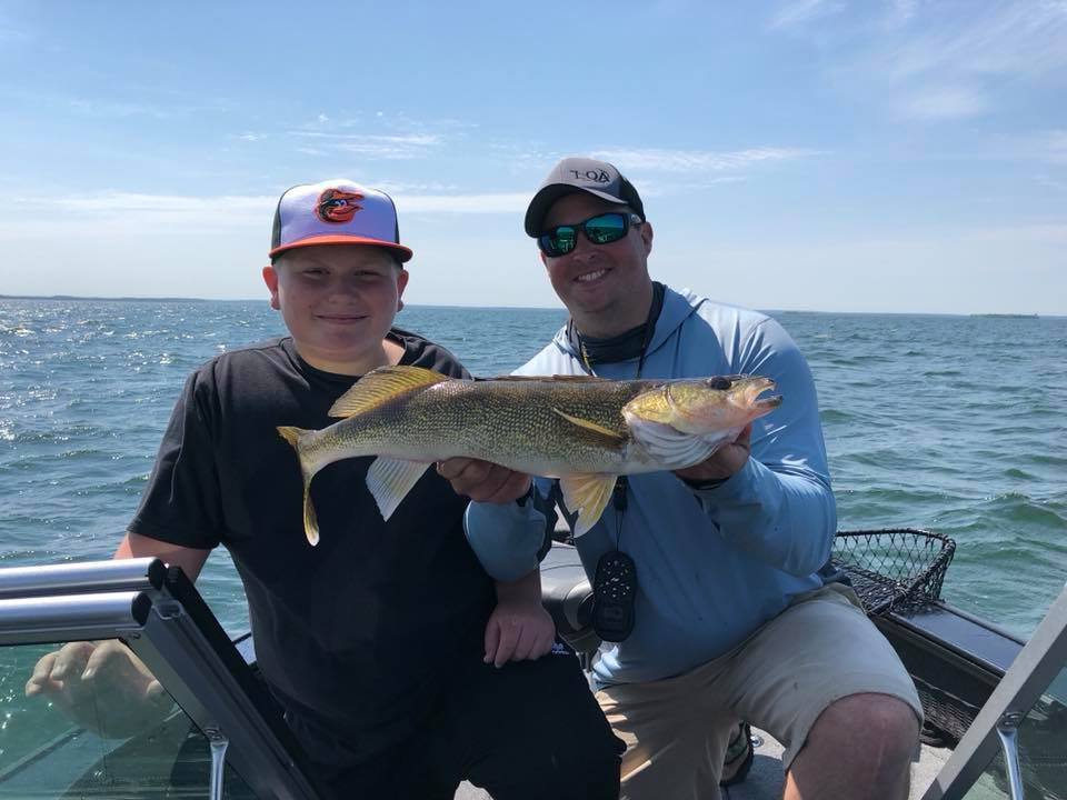 Two men in a boat holding a walleye fish