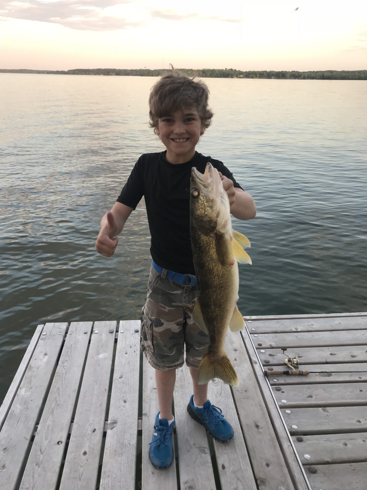 Kid standing on a dock holding a walleye
