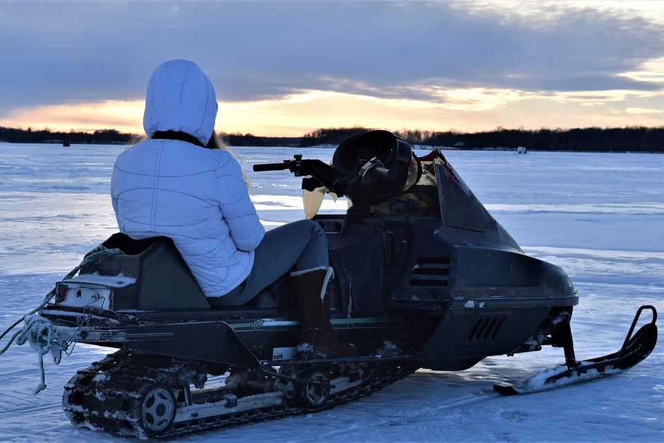 girl on snowmobile on ice
